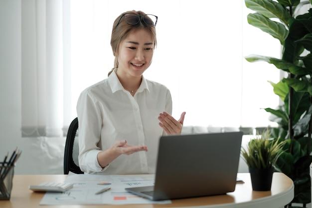 Sorridente jovem funcionária em casa fala conversa em videochamada no laptop com diversos colegas. uma trabalhadora asiática tem uma conferência por webcam ou uma reunião da equipe digital da web ou instruções com colegas de trabalho.