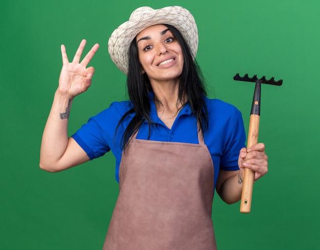 Sorridente jovem jardineira caucasiana vestindo uniforme e chapéu segurando o ancinho fazendo sinal de ok isolado na parede verde