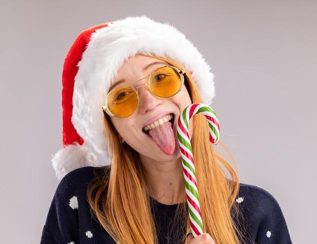 Sorridente jovem linda com chapéu de natal e óculos, segurando e lambendo doces de natal isolados na parede branca