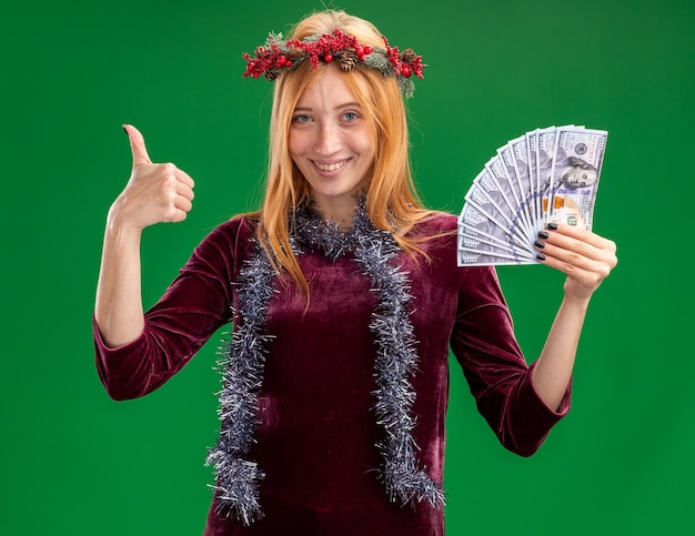 Sorridente jovem linda com um vestido vermelho com coroa e festão no pescoço segurando dinheiro aparecendo o polegar isolado na parede verde