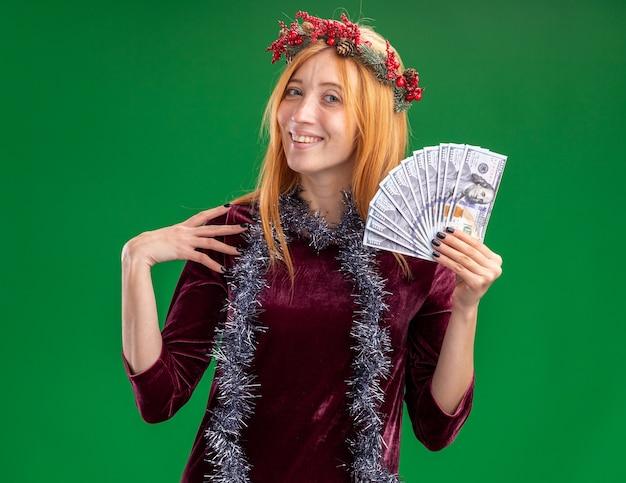 Sorridente jovem linda com vestido vermelho com coroa e festão no pescoço segurando dinheiro, colocando a mão no ombro isolado sobre fundo verde
