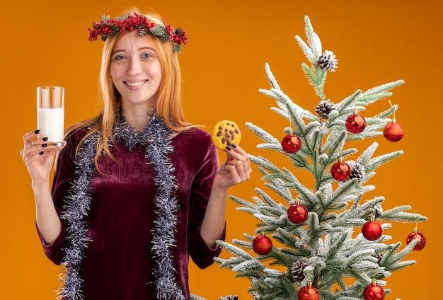 Sorridente jovem linda em pé perto da árvore de natal com vestido vermelho e grinalda com guirlanda no pescoço segurando um copo de leite com biscoitos isolados na parede laranja