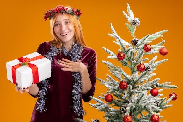 Sorridente jovem linda em pé perto da árvore de natal usando vestido vermelho e grinalda com guirlanda no pescoço segurando uma caixa de presente e colocando a mão em si mesma isolada na parede laranja