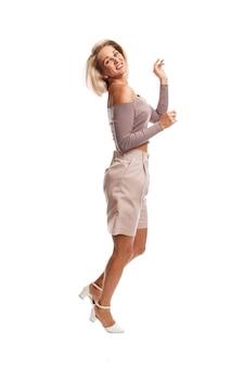 Sorridente jovem loira em um terno rosa pulando. isolado na parede branca.