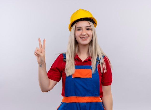 Sorridente jovem loira engenheira construtora de uniforme com aparelho dentário fazendo sinal da paz em um espaço em branco isolado