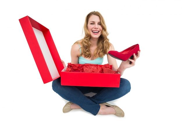 Sorridente jovem mostrando seus novos sapatos