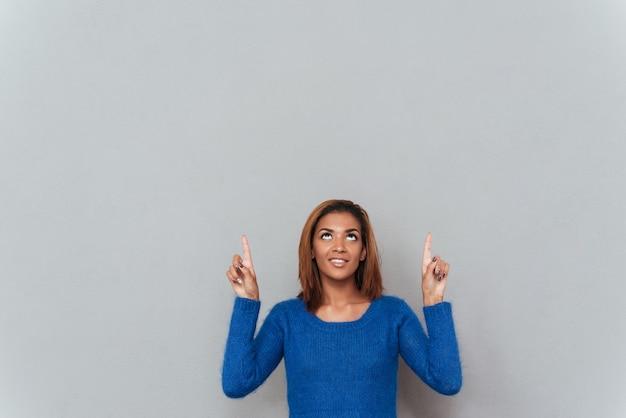 Sorridente jovem mulher africana em suéter apontando os dedos para cima e olhando para cima.