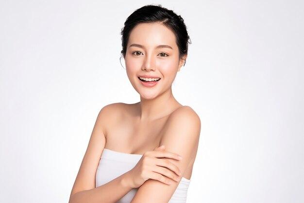 Sorridente jovem mulher asiática bonita com pele limpa, maquiagem natural e dentes brancos,