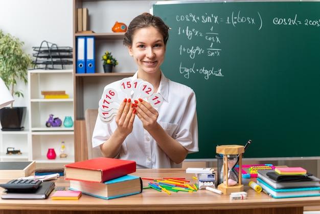 Sorridente jovem professora de matemática sentada na mesa com o material escolar, olhando para a frente, mostrando números de leques na frente da sala de aula