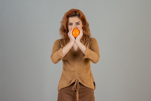 Sorridente jovem ruiva segurando laranja fresca com as duas mãos e olhando para a câmera.