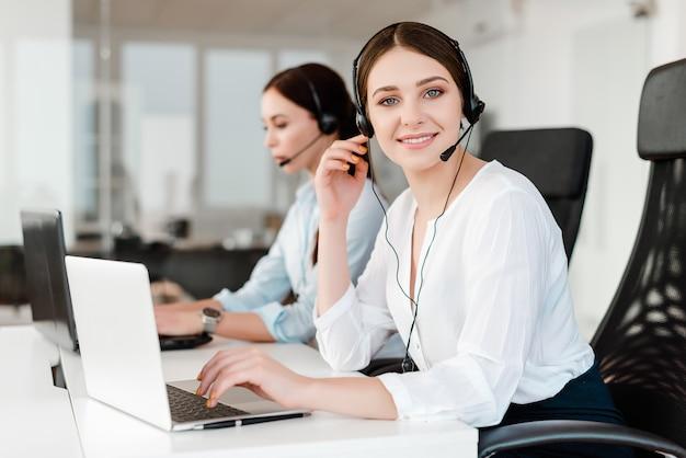 Sorridente jovem trabalhador de escritório com um fone de ouvido respondendo em um call center