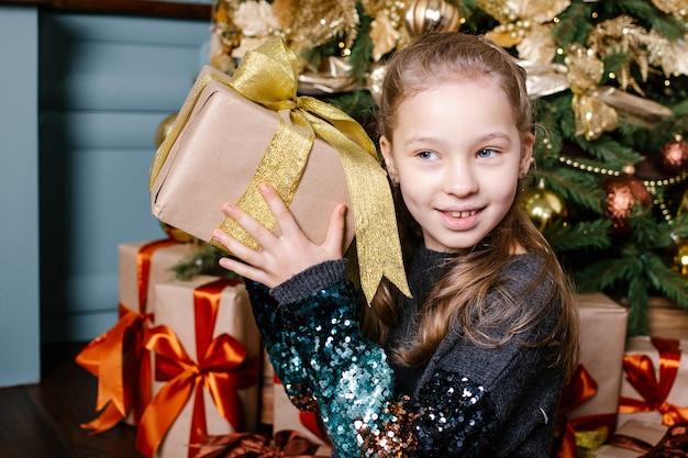 Sorridente linda menina criança segurando o presente de natal na mão perto da árvore de natal.