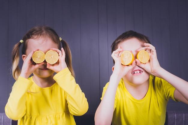 Sorridente linda menina e menino em camisas amarelas, segurando metades de frutas frescas de limão azedo perto dos olhos e sobre fundo cinza de madeira.