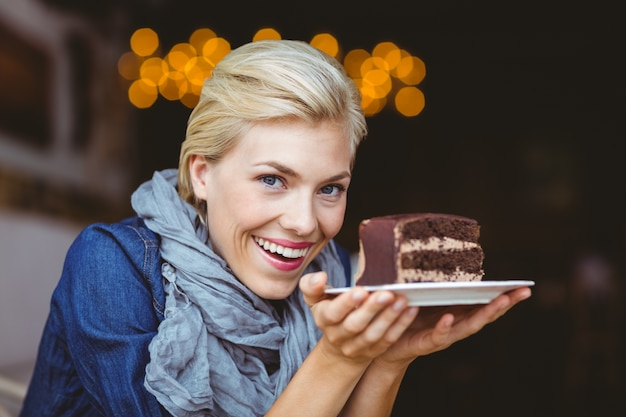 Sorridente loira segurando um bolo de chocolate
