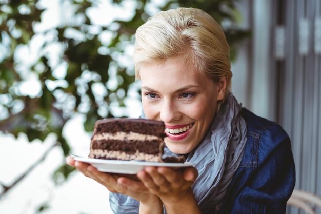 Sorridente loiro olhando um bolo de chocolate