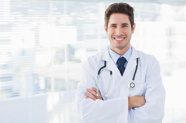 Sorridente médico cruzou os braços e olhou para a câmera