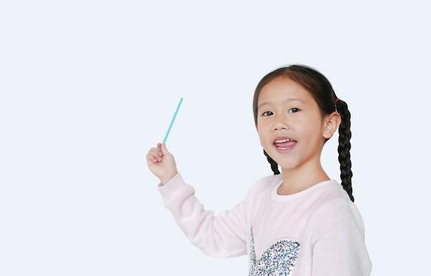 Sorridente menina asiática apontando para cima presente algo