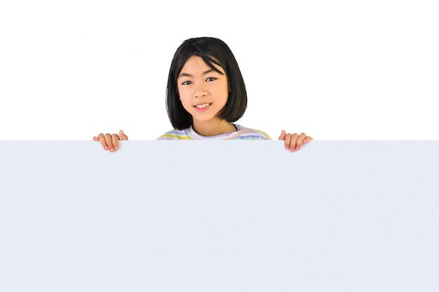 Sorridente menina asiática com placa branca em branco para o lugar de publicidade para você, garoto segurando o tabuleiro vazio, isolado na parede branca