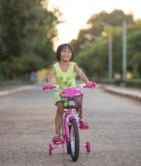 Sorridente menina bonitinha com bicicleta na estrada