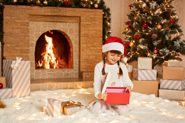 Sorridente menina bonitinha vestindo suéter branco e chapéu de papai noel, posando na sala festiva com lareira e árvore de natal, segurando a caixa de presente de natal aberta.