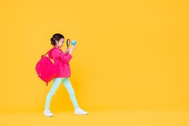 Sorridente menina cute com cabelo pigtail espreitar através de uma lente de aumento