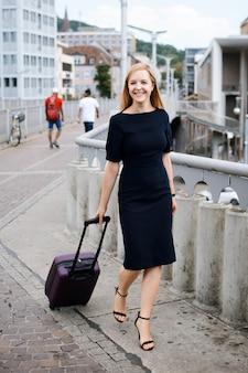 Sorridente menina de negócios chegou a uma nova cidade nos negócios