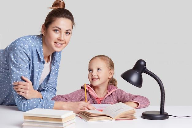 Sorridente menina encantadora senta-se à mesa, faz lição de casa, juntamente com sua mãe, tenta escrever composição, olhar com alegria, usa lâmpada de leitura para uma boa visão, isolada na parede branca