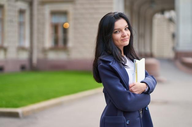 Sorridente menina estudante morena segurando os cadernos e livros didáticos, fica na universidade