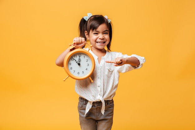 Sorridente menina segurando o relógio despertador.