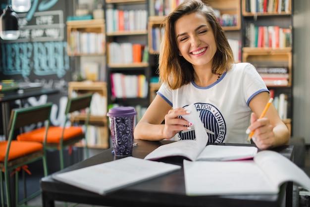 Sorridente menina sentada na mesa com cadernos