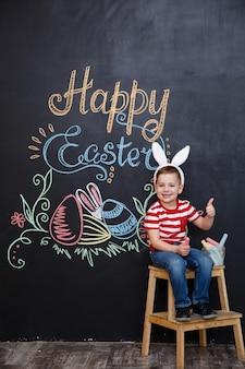 Sorridente menino bonitinho wearring orelhas de coelho de páscoa