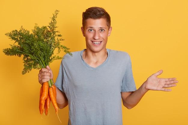 Sorridente menino bonito, espalhando a mão de lado e segurando o monte de cenouras na outra mão