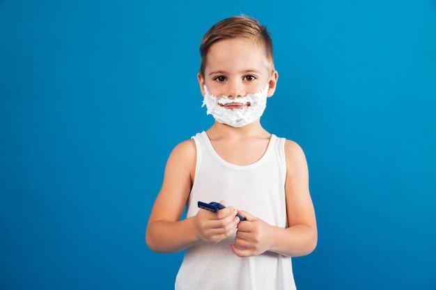 Sorridente menino em espuma de barbear segurando a navalha