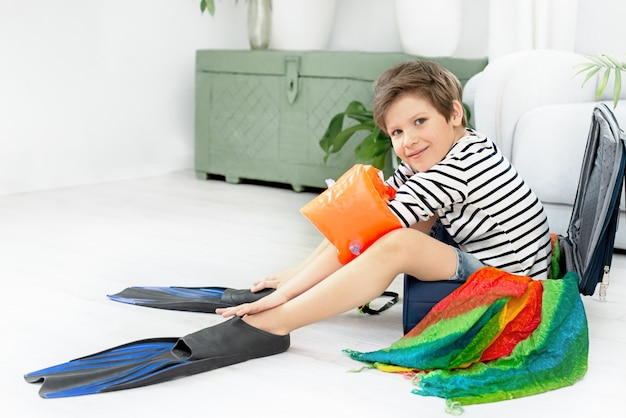 Sorridente menino engraçado turista sentado em uma mala em nadadeiras, sentado em casa