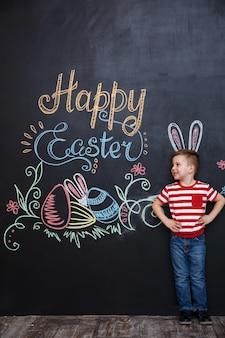 Sorridente menino feliz com orelhas de coelho em pé
