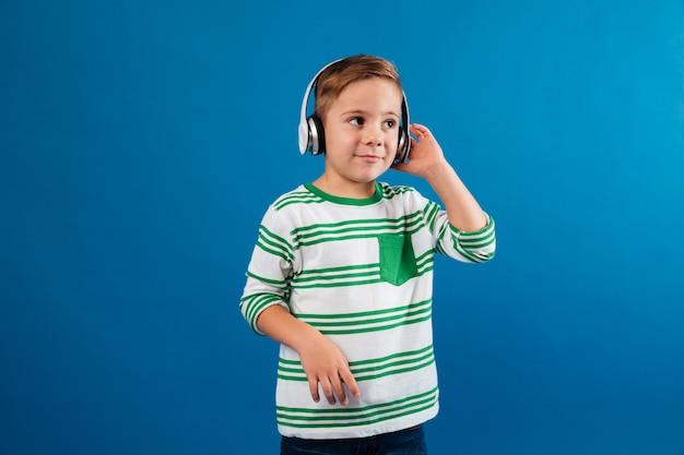 Sorridente menino ouvindo música pelo fone de ouvido e olhando de lado