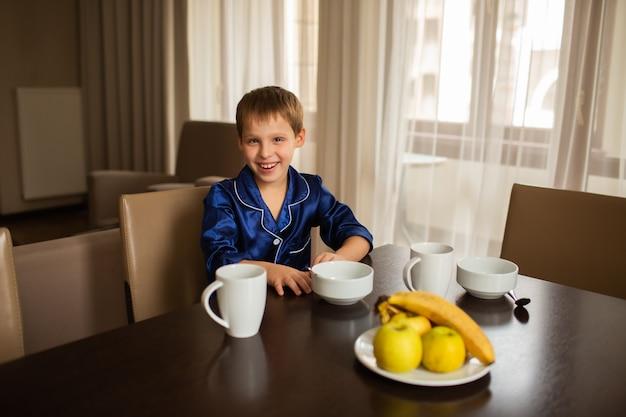Sorridente menino senta-se à mesa de jantar e come alimentos saudáveis frutas e mingau