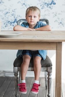 Sorridente menino sentado na cadeira em frente a mesa de jantar de madeira