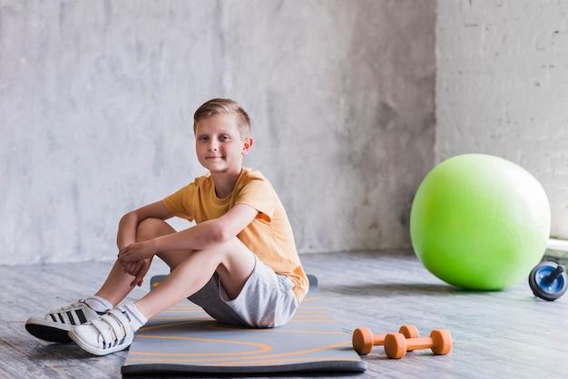 Sorridente menino sentado no colchonete com halteres; slide de bola e rolo de pilates