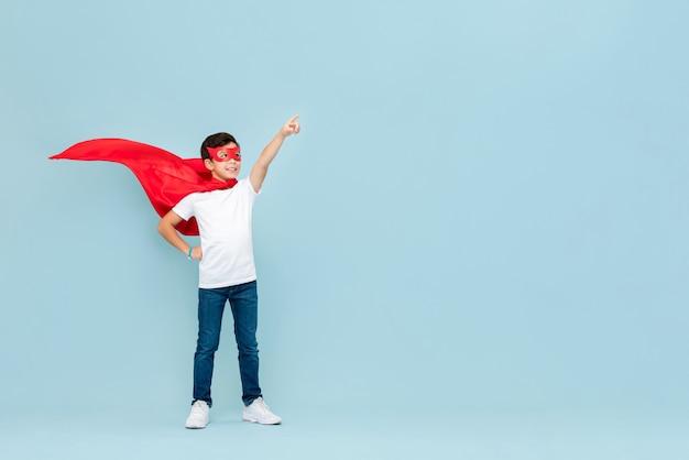 Sorridente menino super-herói em máscara vermelha e capa apontando a mão de lado
