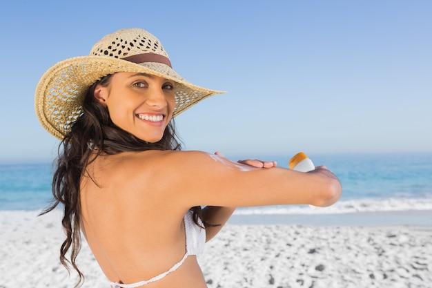 Sorridente morena atraente com chapéu de palha colocando creme solar