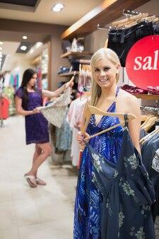 Sorridente mulher de pé ao lado do trilho de roupas