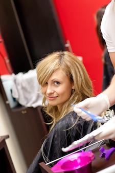 Sorridente, mulher loira, secando o cabelo