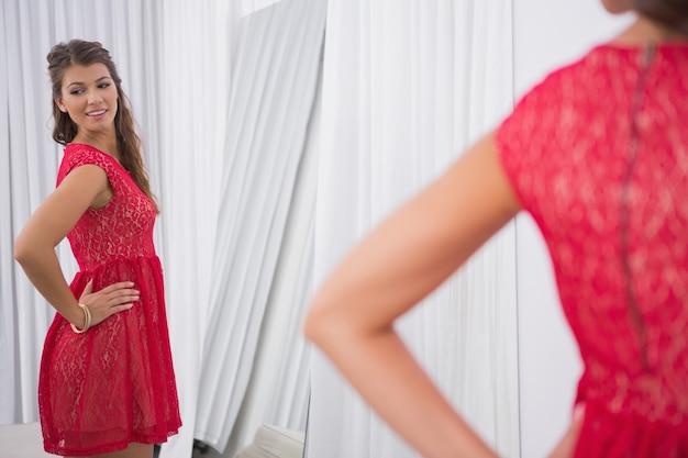 Sorridente mulher olhando para si mesma no espelho