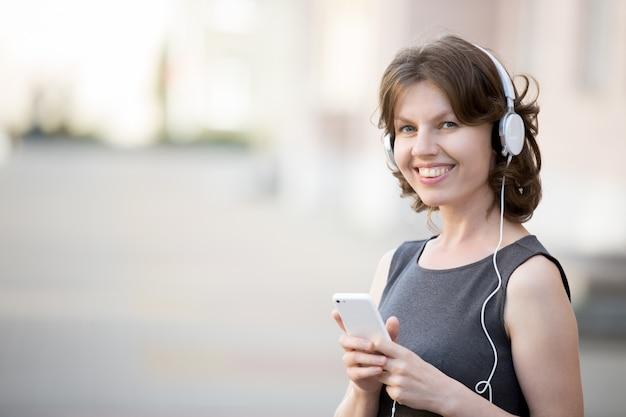 Sorridente, mulher ouvindo música online