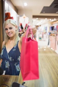 Sorridente mulher passando saco de compras