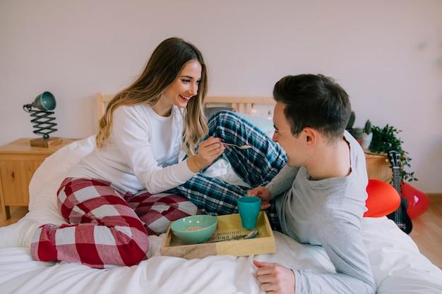 Sorridente mulher que alimenta o homem na cama