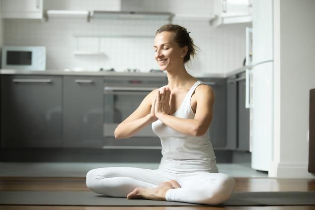 Sorridente mulher sentada no half lotus exercício