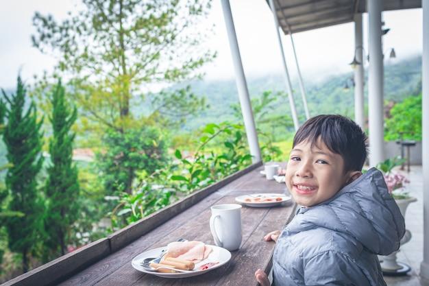 Sorridente rapaz asiático está tomando café da manhã em um fundo natural bonito
