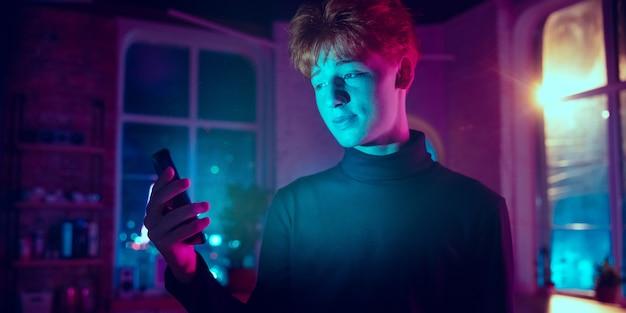 Sorridente. retrato cinematográfico do homem ruivo elegante no interior iluminado por néon. tons de efeitos de cinema em azul-púrpura. modelo caucasiano usando smartphone em luzes coloridas dentro de casa. folheto.